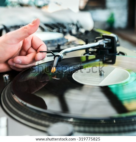 Dj mixes track on vinyl player in club at party - stock photo