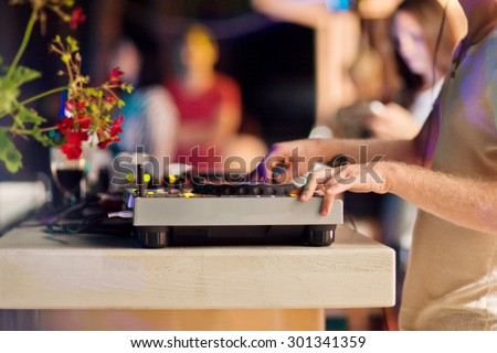 DJ mixing music on console at the night club - stock photo
