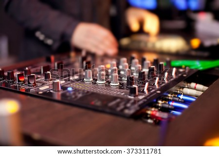 DJ mixing music on console at the night club. - stock photo
