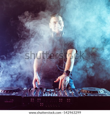 DJ mixing music on mixer on dark background
