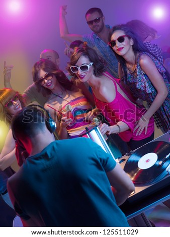dj mixing music with turntables and headphones in front of young dancing people with sunglasses and cocktails surounded by colorful lights - stock photo