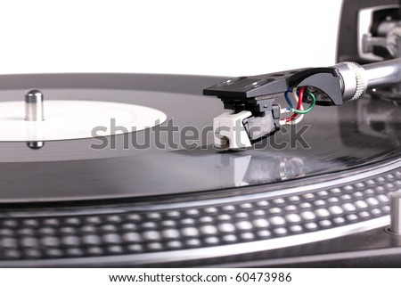 Dj needle on spinning turntable, closed-up on white - stock photo