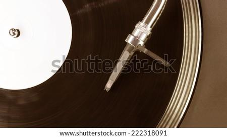 Dj needle stylus on spinning record, closeup - stock photo