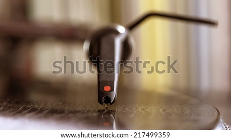 Dj needle stylus on spinning record, vinyl background   - stock photo