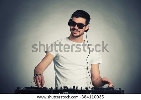 DJ playing music at mixer on grey background - stock photo