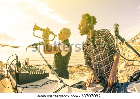 Dj playing summer hits at sunset beach party with trumpet jazz performer - Vacation concept at open air club with house music groove location - Warm vintage sunshine filter with backlight soft focus - stock photo