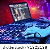 Dj playing the track in the nightclub at a party. In the background laser light show - stock photo