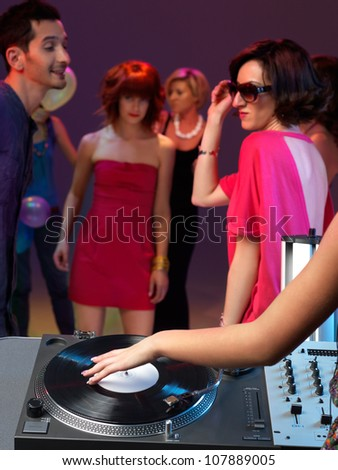 dj's hand working the turntable in a night club - stock photo