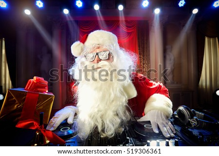 Dj Santa Claus at Christmas with glasses and snow mix on New Year's Eve event in the rays of light.