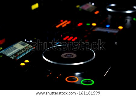 DJ turntable and music deck illuminated at night with colourful lights lighting up the knobs and controls for mixing audio soundtracks and recordings - stock photo