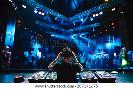 DJ with headphones at night club party under the blue light and people crowd in background - stock photo