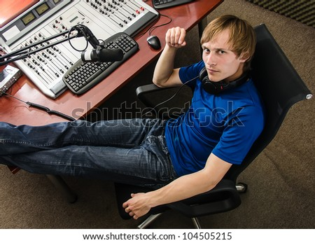 Dj working in front of a microphone on the radio, from the top - stock photo