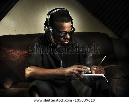 dj writing lyrics on note book in studio - stock photo