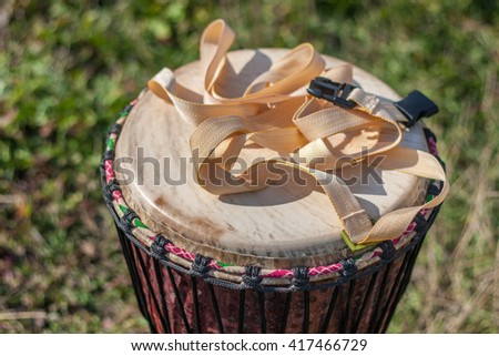 Djembe drum at green grass background. Closeup. - stock photo