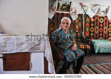 Dnepropetrovsk, Ukraine - 25 August 2009: A woman 80-85 years in rural cottage decorated in traditional style on the background of the carpet, pictures, towels