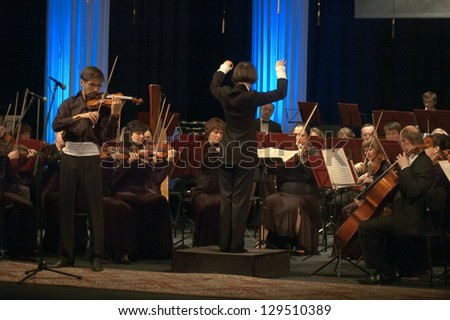 DNEPROPETROVSK, UKRAINE - FEB. 25: Violinist Emanuel Salvador (Portugal) and Symphonic Orchestra - main conductor Ponomarchuk perform music of Tchaikovsky on Feb. 25, 2013 in Dnepropetrovsk, Ukraine - stock photo