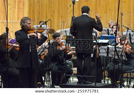 DNIPROPETROVSK, UKRAINE -? FEBRUARY 23: Famous violinist Alksandr Trostyansky and Youth Symphony Orchestra FESTIVAL  perform at the Conservatory on Feb. 23, 2015 in Dnipropetrovsk, Ukraine - stock photo
