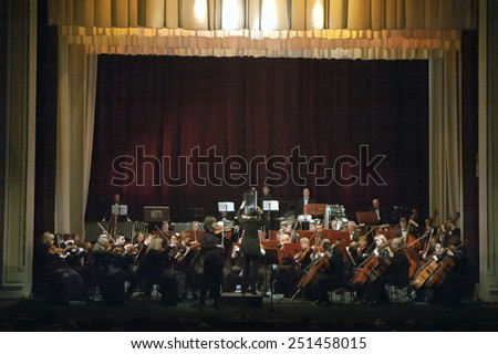 DNIPROPETROVSK, UKRAINE - FEBRUARY 9: Famous Violinist Dmitry Tkachenko and Academic Symphony Orchestra perform at the State Russian Drama Theatre on February 9, 2015 in Dnipropetrovsk, Ukraine - stock photo