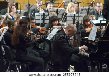 DNIPROPETROVSK, UKRAINE - FEBRUARY 23: Pianist Vyacheslav Poprugin and Youth Symphony Orchestra FESTIVAL perform at  the Conservatory on February 23, 2015 in Dnipropetrovsk, Ukraine - stock photo