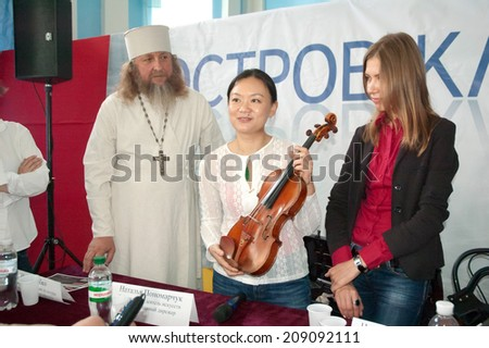 """DNIPROPETROVSK, UKRAINE - JUNE 23: Famous violinist Qian Zhou is Gvadanini violin during a press conference of the musical project """"Island Classics"""" on June 23, 2014 in Dnipropetrovsk, Ukraine - stock photo"""