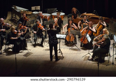 DNIPROPETROVSK, UKRAINE - JUNE 22, 2015:  FOUR SEASONS Chamber Orchestra - main conductor Dmitry Logvin perform at the State Russian Drama Theatre - stock photo
