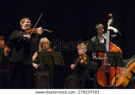 DNIPROPETROVSK, UKRAINE - MAY 14: Famous violinist Ostap Shutko and members of the Symphony Orchestra perform at the State Russian Drama Theatre on May 14, 2015 in Dnipropetrovsk, Ukraine - stock photo