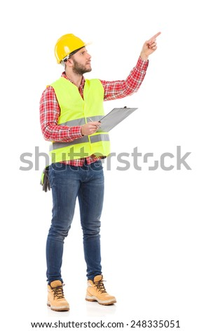 Do it right. Manual worker in yellow helmet and reflective waistcoat holding clipboard and pointing. Full length studio shot isolated on white. - stock photo