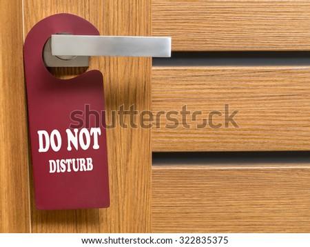 Do Not Disturb door hanger hanging on hotel room door handle - stock photo