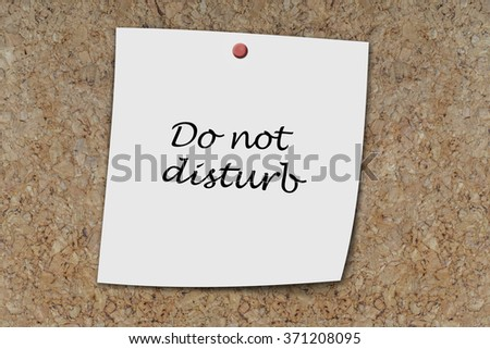 do not disturb written on a memo pinned on a cork board - stock photo
