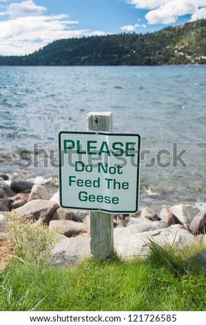 Do not feed the geese sign on outdoor park by the lake