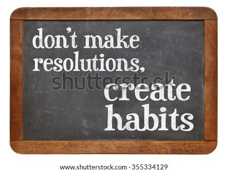 Do not make resolutions, create habits - advice on a vintage slate blackboard - stock photo