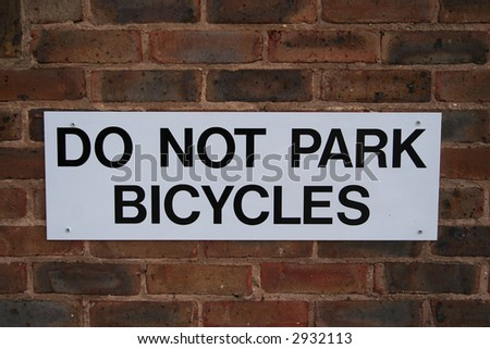 do not park bicycles sign on brick wall