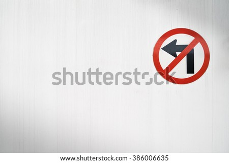 Do-not-turn-left sign with red crossing on an old white wall with some shadow