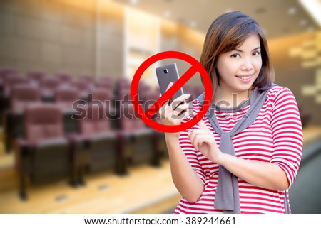 Do not use telephone sign with young smiling student holding smartphone in meeting or studying room - stock photo