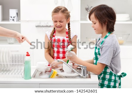 Do the dishes - upset kids ordered to help in the kitchen by washing tableware - stock photo