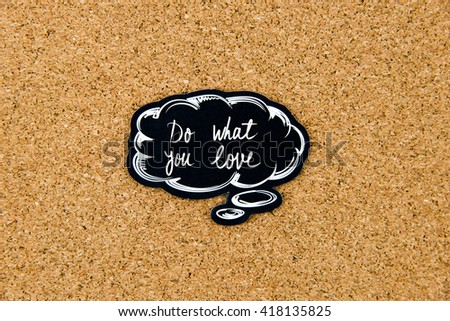 DO WHAT YOU LOVE written on black thinking bubble over cork board background, copy space available - stock photo