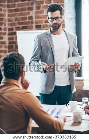 Do you have any suggestion? Young handsome man wearing glasses holding digital tablet and discussing something while his coworkers listening to him sitting at the office table - stock photo