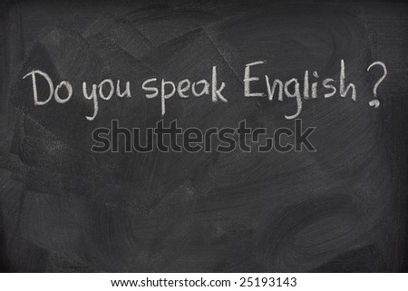 do you speak English question handwritten with white chalk on a blackboard with eraser smudges - stock photo