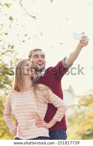 Do yourself a photo. Loving couple photographed together on a mobile phone. Happy couple in love taking self-portrait photo on City Park. Young tourists having fun date. Asian man, caucasian woman. - stock photo