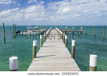 dock and boat with turquoise waters in bahamas - stock photo