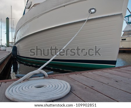 Dock cleat with a white line tied around it, then coiled beside the cleat.  boat secured to boat dock in background - stock photo