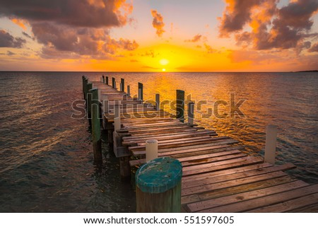 Dock during caribbean sunset, beautiful orange yellow colors and perspective of this boat dock and fishing dock in Eleuthera island, Bahamas