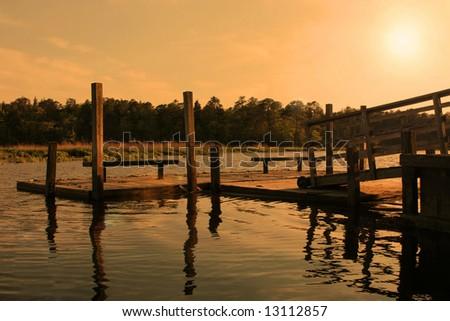 dock extending over lake during sunset - stock photo