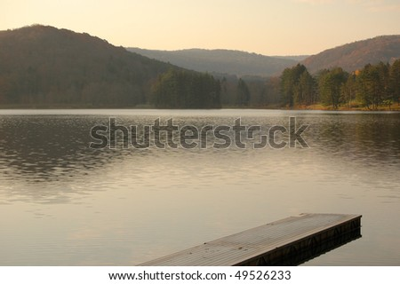 dock into a lake, with a forest and hills - stock photo