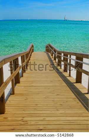 Dock Leading to Beautiful Water with Sailboat in Distance
