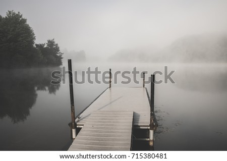 Dock on the lake in the early morning fog at Wolf Run State Park in Ohio with trees reflecting on the water