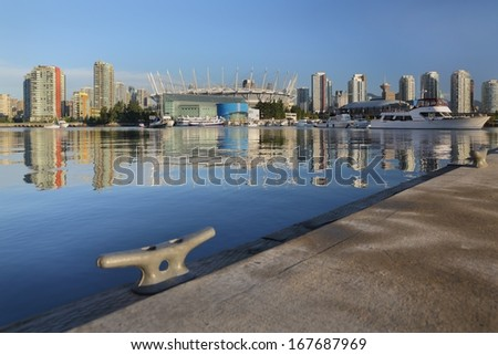 Dock View, False Creek, Vancouver. An early morning view of the downtown Vancouver skyline reflected in the still waters of False Creek from a floating dock. British Columbia, Canada.  - stock photo