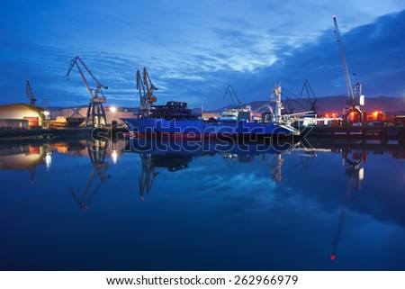dock with cranes and a ship at night