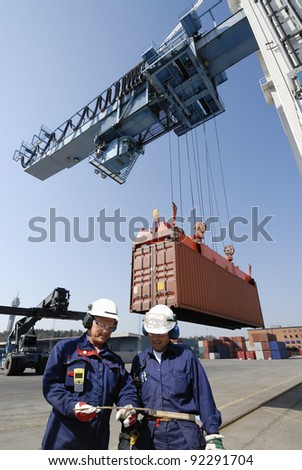 dock workers in container-port, cranes and trucks inside commercial dock. - stock photo