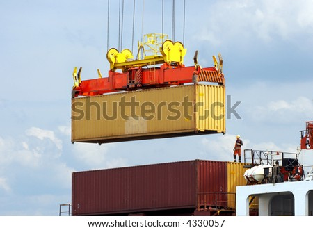 Dockworker checking the precise placement of a container on a ship. Every brandname has been removed and his face has been made unrecognizable. - stock photo